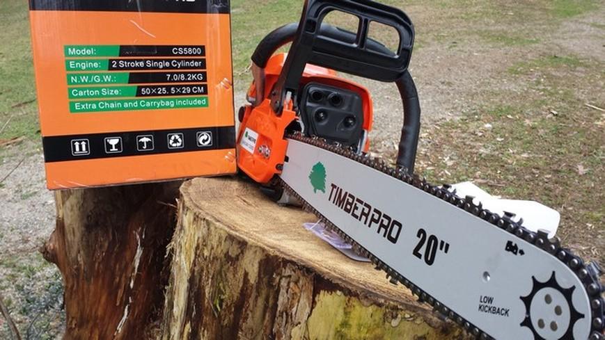 motosierra Timberpro y su embalaje sobre un tronco de madera